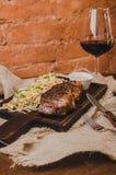烤ribeye牛排用炖煮的食物圆白菜和葡萄酒杯红葡萄酒、草本和香料在棕色麻袋布在木 免版税库存图片
