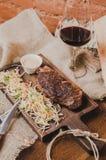 烤ribeye牛排用炖煮的食物圆白菜和葡萄酒杯红葡萄酒、草本和香料在棕色麻袋布在木 库存照片