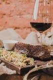 烤ribeye牛排用炖煮的食物圆白菜和葡萄酒杯红葡萄酒、草本和香料在棕色麻袋布在木 免版税图库摄影