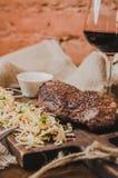 烤ribeye牛排用炖煮的食物圆白菜和葡萄酒杯红葡萄酒、草本和香料在棕色麻袋布在木 库存图片