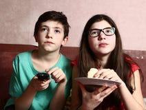 麻烦和姐妹手表电影与遥控 免版税库存图片