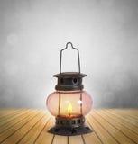 烧与在木头之间的明亮的火焰的老煤油提灯 库存照片