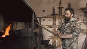 烧与空气的有胡子的人铁匠原始的伪造壁炉在历史铁匠铺户内 股票录像