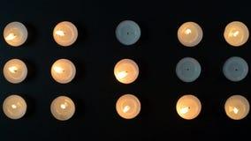 烧和退色由在黑背景的风的十五个蜡烛英尺长度  股票录像