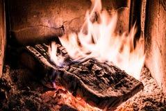 烧在与炭烬发光的老火炉的木头 库存图片