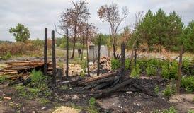 烧在房子下在路附近 免版税库存图片