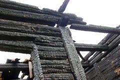 烧在木房子下,被烧焦的墙壁,被烧的屋顶 免版税库存图片