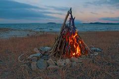 烧在海滩的火在晚上 明亮的火,木柴 图库摄影