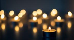 烧在背景蓝色颜色的许多蜡烛火焰  免版税库存照片