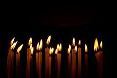 烧在黑背景的晚上的许多圣诞节蜡烛 库存照片