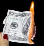 烧在黑背景的100美元 免版税库存图片