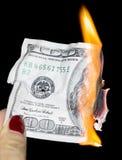 烧在黑背景的100美元 免版税库存照片