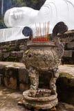 烧在说谎的Buddah雕象外面的棍子 免版税库存图片