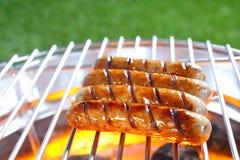 烧得发嘶声在一串热的烤肉的香肠 免版税库存照片