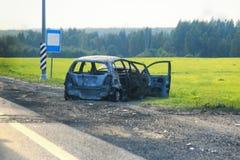 烧成灰烬汽车击毁在路一边 库存照片