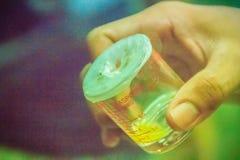 烧杯收集产物的s被挤奶的绿色坑蛇蝎毒液 库存照片