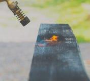 烧焦了委员会由煤气喷燃器的火焰处理 图库摄影
