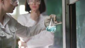烧瓶的年轻女人热在医学实验室 股票录像