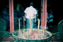 烧繁忙的香火smokey寺庙的佛教徒 免版税库存图片