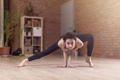 热切站立年轻亭亭玉立的妇女做舒展弯曲向前面朝下的锻炼户内在健身俱乐部 免版税库存图片