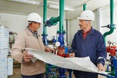 热化工程师安装工在锅炉室 免版税库存照片