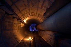 热化输送管圆的地下隧道与生锈的管的 库存照片