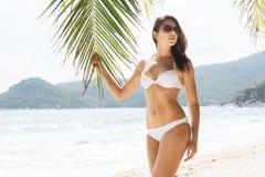 热和美丽的女孩佩带的太阳镜和引诱的白色游泳衣 库存照片