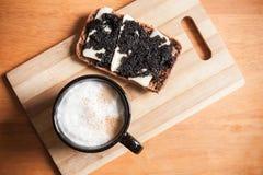 热奶咖啡和一个三明治用黑鱼子酱 库存图片