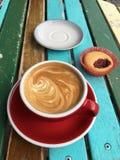 热奶咖啡和蛋糕在早晨阳光下 免版税图库摄影
