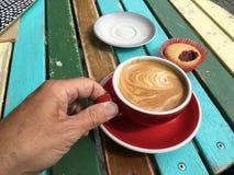 热奶咖啡和蛋糕在早晨阳光下 免版税库存图片