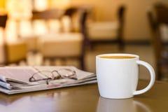 热奶咖啡在木桌上的咖啡杯与报纸 免版税库存图片