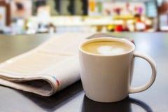 热奶咖啡在木桌上的咖啡杯与报纸 库存照片