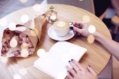 热奶咖啡拿铁咖啡在有心脏的妇女手上在上面 在木桌上的花在现代咖啡馆 St华伦泰庆祝concep 免版税库存图片