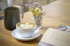 热奶咖啡有装饰花和被打开的书的咖啡杯 免版税图库摄影