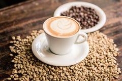 热奶咖啡杯子和咖啡豆静物画  库存图片