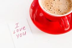 热奶咖啡杯子和笔记我爱你关于轻的土气表 库存图片