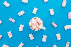 热奶咖啡杯子用在蓝色背景的含糖的蛋白软糖 平的位置,顶视图 库存图片