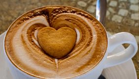 热奶咖啡用心形的饼干 免版税库存照片