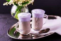热奶咖啡用淡紫色和巧克力糖浆和花 免版税库存照片