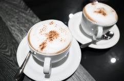热奶咖啡,两杯咖啡用牛奶起泡沫 库存照片