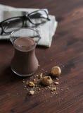 热巧克力、杏仁饼和报纸黑褐色木表面上 免版税库存照片
