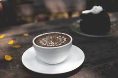 热巧克力在木桌上的拿铁艺术 免版税库存图片