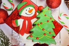 热巧克力杯子用蛋白软糖、姜饼雪人和圣诞节礼物在白色木背景 库存图片