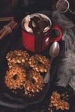 热巧克力用在一个红色杯子和饼干的蛋白软糖与坚果 土气样式,与定调子的黑暗的照片 库存图片