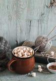 热巧克力用在一根陶瓷杯子、旧书、毛线和针的蛋白软糖 库存图片
