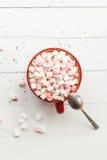 热巧克力用在红色杯子的蛋白软糖在桌上 库存图片