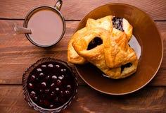 热巧克力用开胃小圆面包 在一个玻璃花瓶的樱桃果酱 甜小圆面包用蓝莓在木板阻塞 库存照片