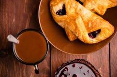 热巧克力用开胃小圆面包 在一个玻璃花瓶的樱桃果酱 甜小圆面包用蓝莓在木板阻塞 图库摄影