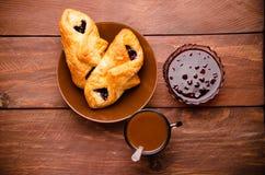 热巧克力用开胃小圆面包 在一个玻璃花瓶的樱桃果酱 甜小圆面包用蓝莓在木板阻塞 免版税库存照片