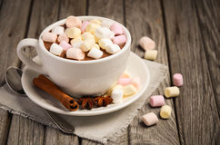 热巧克力用蛋白软糖和香料在土气木桌上 免版税库存图片